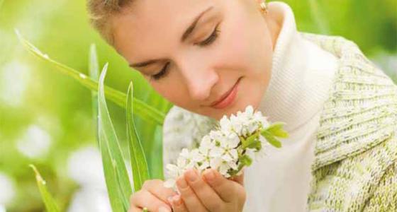 Frau riecht an Frühlingsblumen